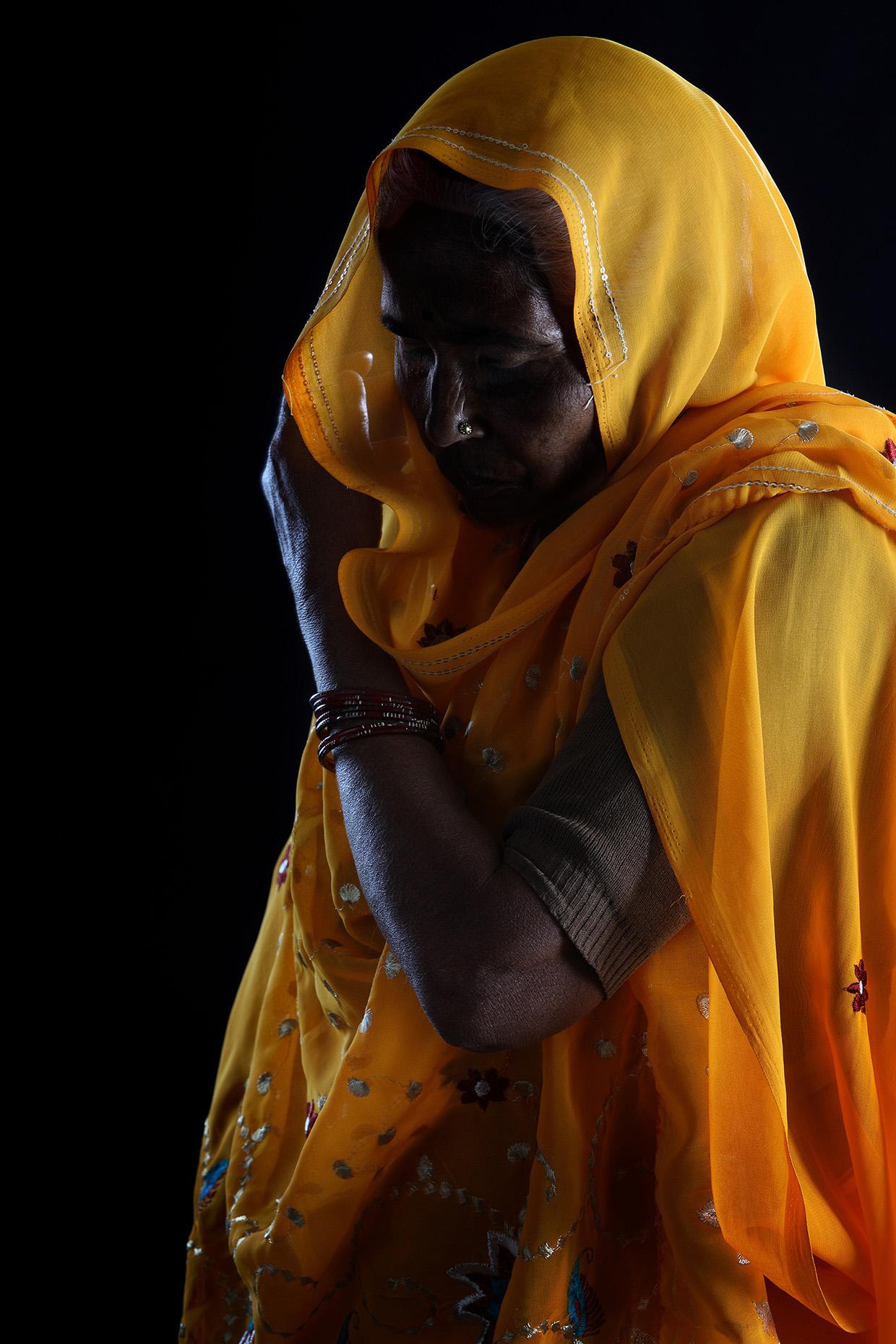 Portrait of old woman wearing a yellow sari at the Kumbh Mela