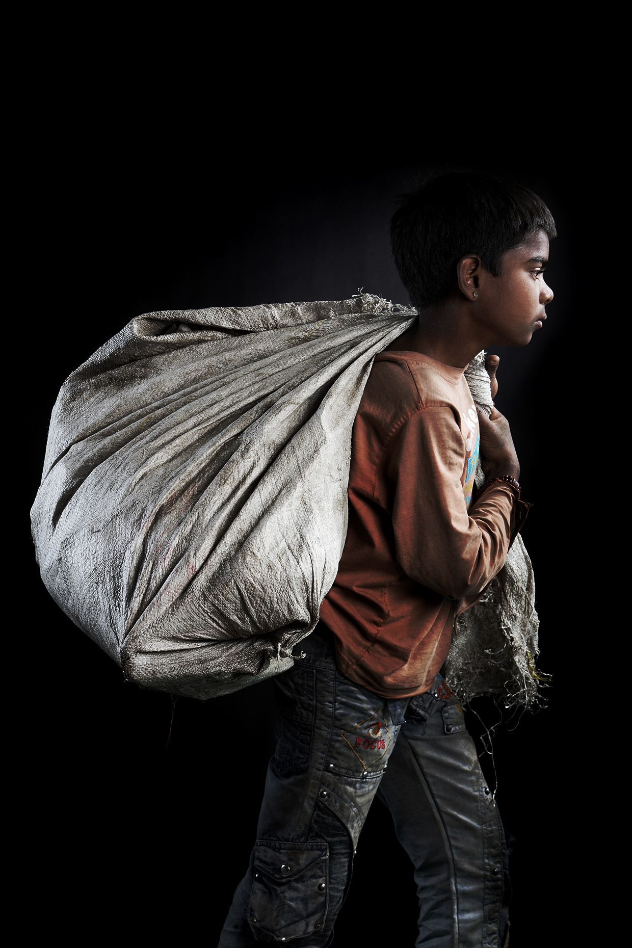 Portrait of garbage boy carrying a bag on his shoulder.