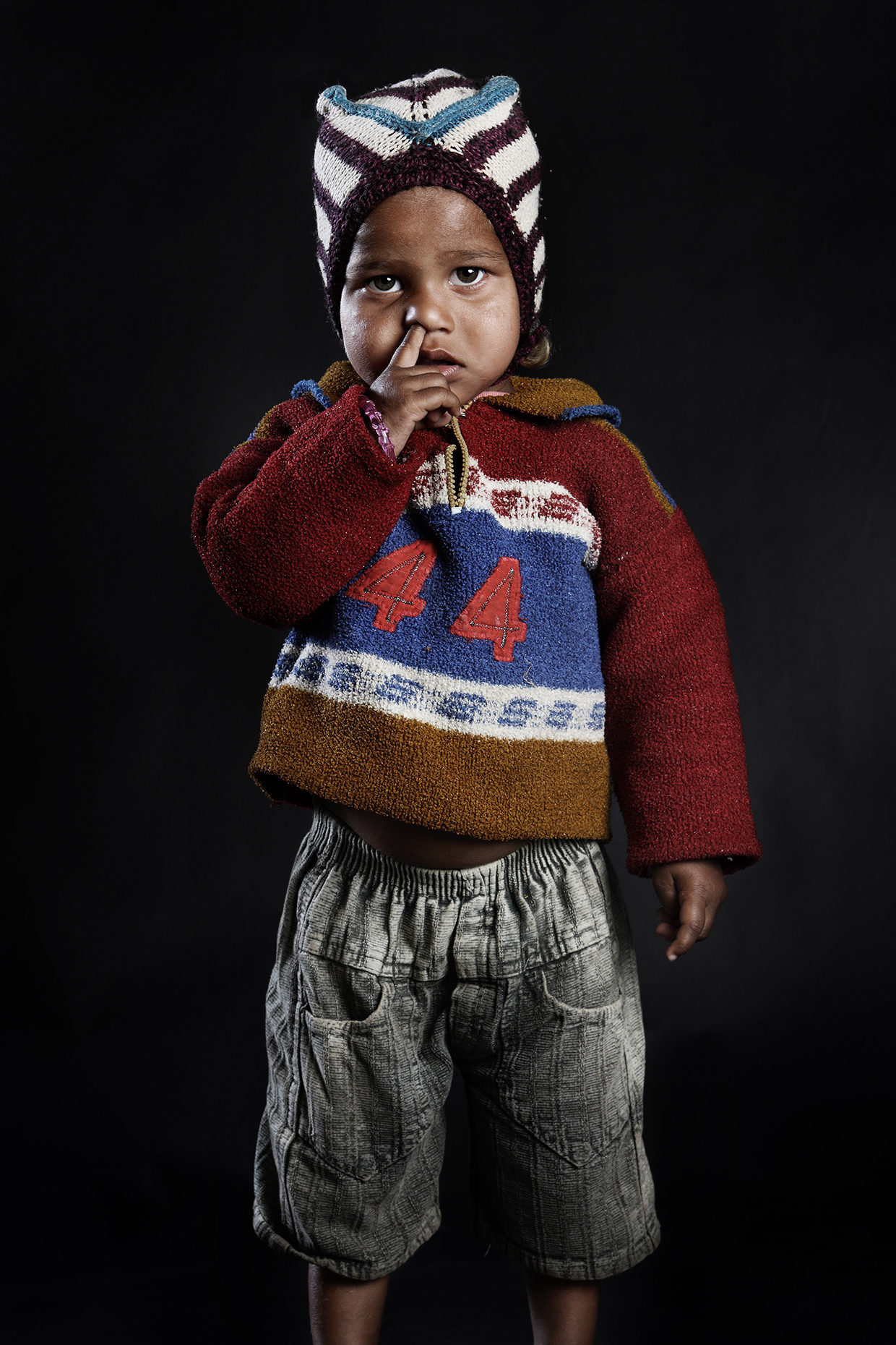 Child posing in front of the camera with his finger in the nose