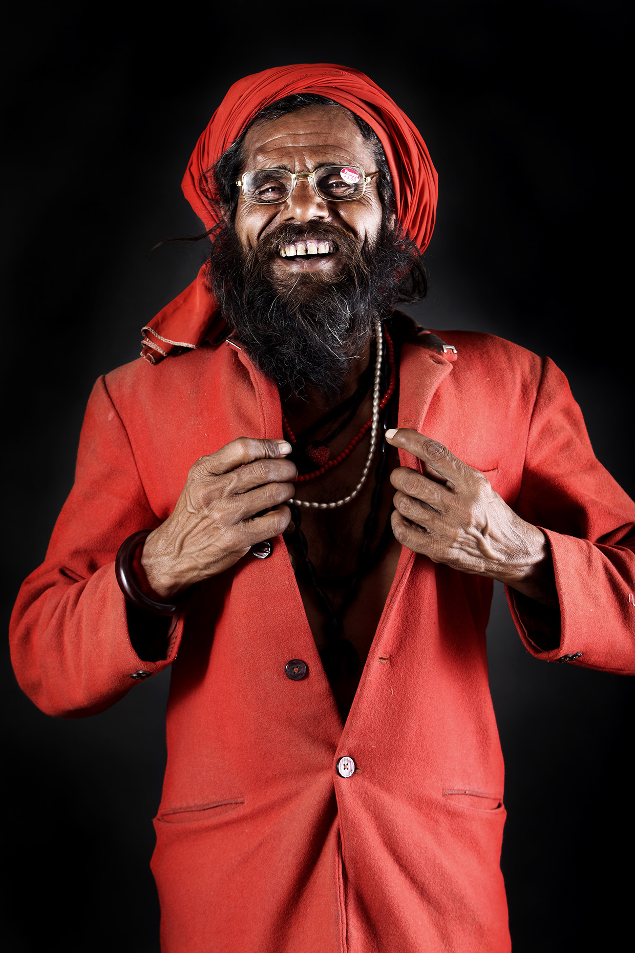 Photo of bearded man with red suit at the Kumbh Mela