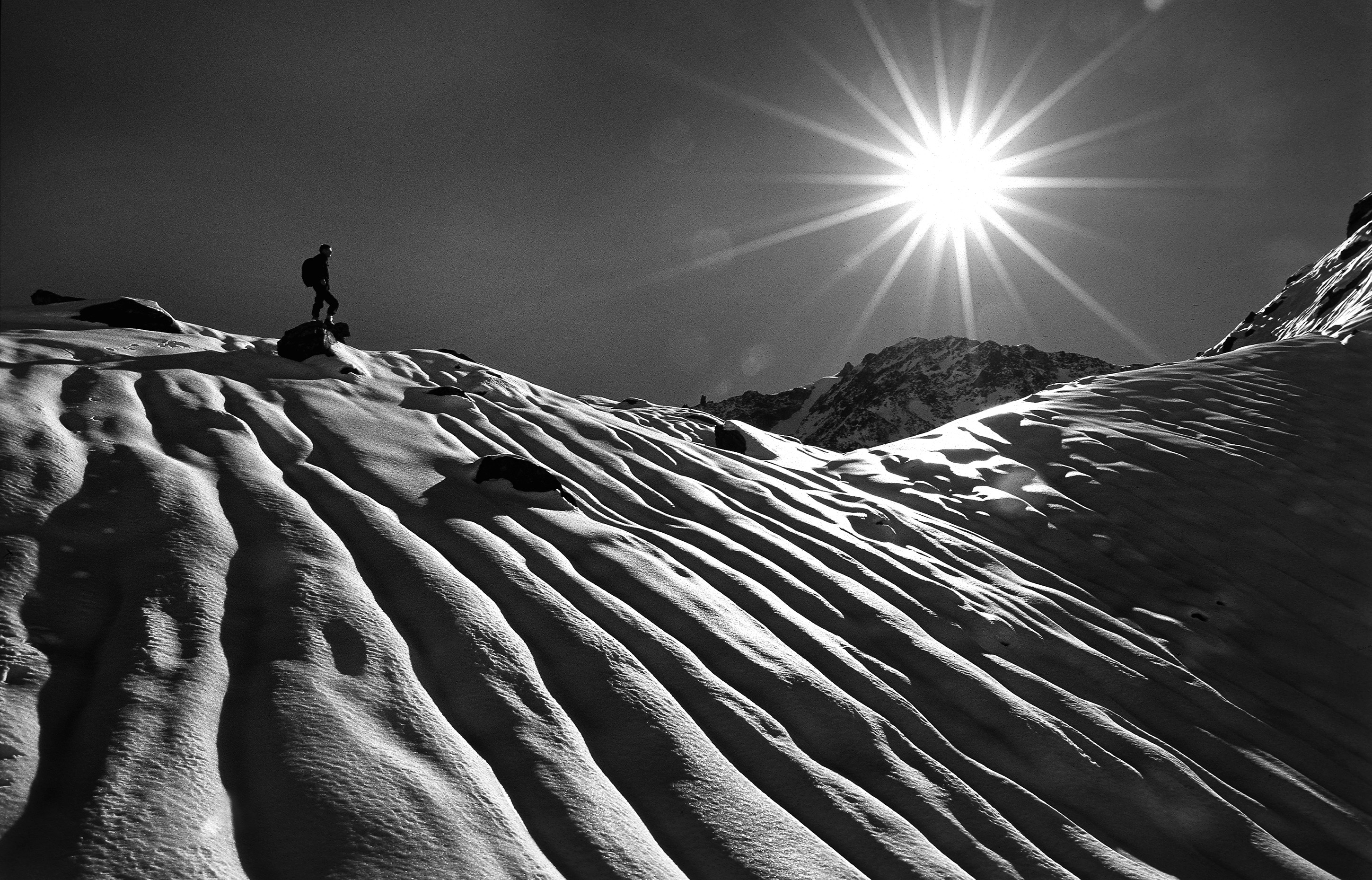 Man facing the sun and standing on the edge of a snowy mountain